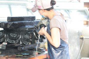 石を磨く女性