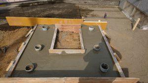 打設工。型枠の中にコンクリートを流して均します。養生期間をおいて型枠を外すと基礎工事の完成です。