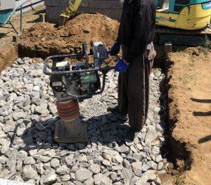 転圧工。根掘工の上から砕石を敷き詰めてランマー等でしっかりと踏み固めます。