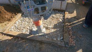 転圧工。砕石を敷き詰めてランマーなどでしっかりと踏み固めます。