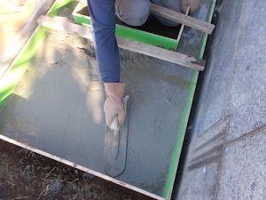 コンクリート打設工を行います。型枠にコンクリートを流し込みコテで均一に均します。
